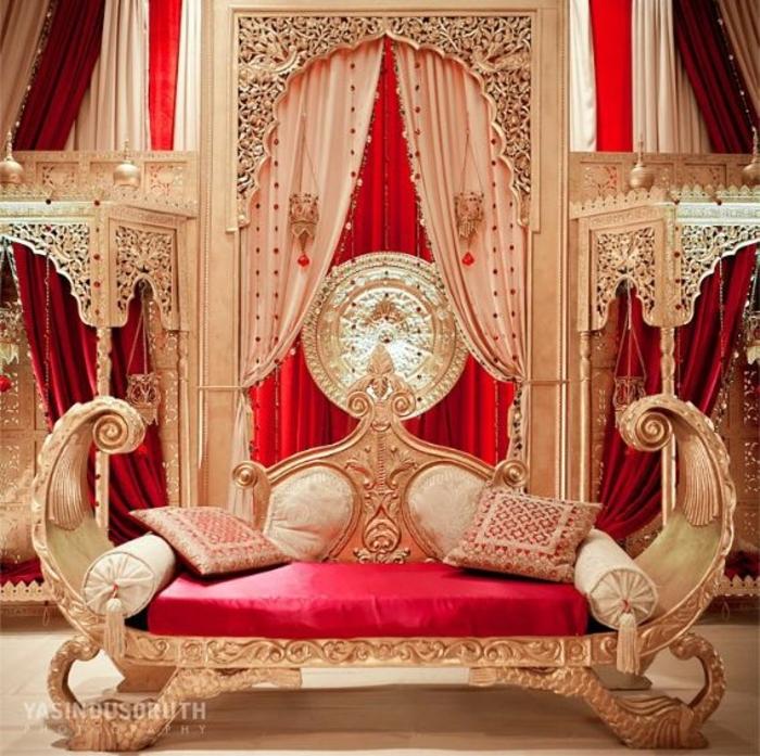 Einrichtung im Aladin-Stil - Liege mit Holzbeinen, gestrichen in Goldfarbe, Designer-Couch aus Massivholz, rundde Kissen mit Troddeln, Wandverkleidung mit Schnitzerei, runde Wanddeko aus Gold, lange rote schwerfallende Gardinen