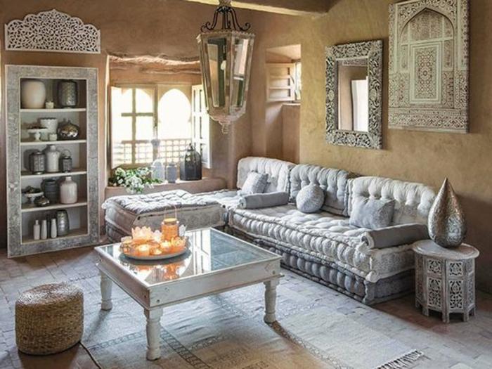 Regal integriert in eine Wandnische, Regal mit Keramikgefäßen, Wandspiegel mit breitem Rahmen, weiße Couch mit kleinen Couchkissen, weiße Teppiche auf dem weißgestrichenen Holzboden, Beistelstiltisch mit vielen Ornamenten, quadratischer Tisch aus Glas und Holz, kleines Fenster in der Ecke des Zimmers