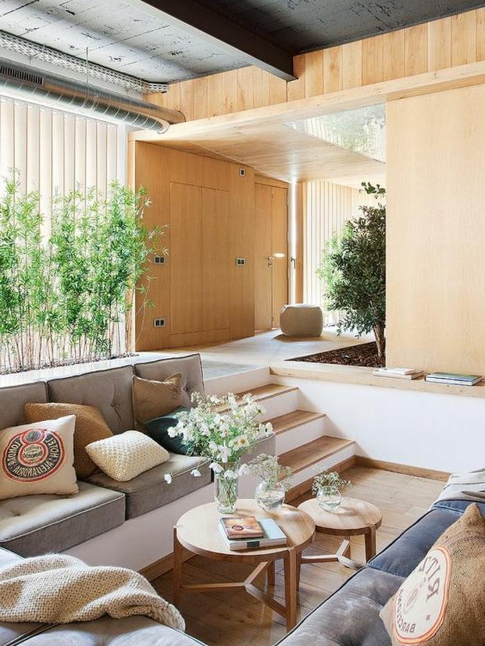 tief liegende Relaxecke mit einem Tischsatz aus zwei hölzernen Tischen, ein Strauß weiße Blumen in einer Glasvase, Wandverkleidung aus hellem Holz, Innen-Gartenbereich im Wohnzimmer