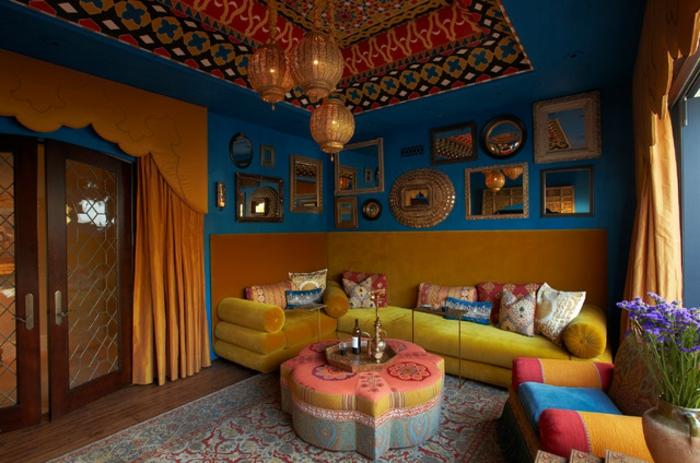 blaue Wände mit vielen Spiegeln und Bildern, gelbe Polstercouch in der linken Ecke, Wandverkleidung aus Polster, die als Rückenlehne dient, ovaler Polstertisch in der Form einer Blume, Polstersessel in vielen Farben, großer Musterteppich in Blau und Terrakotta, Glastür mit zwei Flügeln, Tür mit orangenem Vorhang, Zimmerdecke mit dekorativer Nische, Lavendelstrauß in einem Keramikgefäß