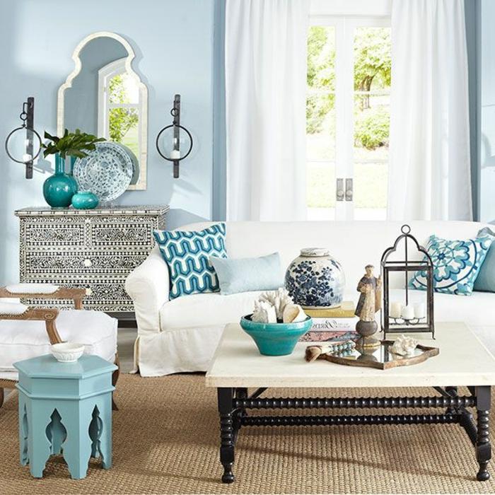 Wohnzimmer mit hellblauer Wand, lange weiße Gardinen, dekoratives Spiegel mit schmalem weißen Rahmen, dekorativer Teller in zwei Farben, Beistelltisch aus Holz, gestrichen in Hellblau, weißer Tisch mit schwarzen Holzbeinen aus ahagoniholz, Musterkissen in blauer Farbe, viele Dekoelemente auf dem Tisch