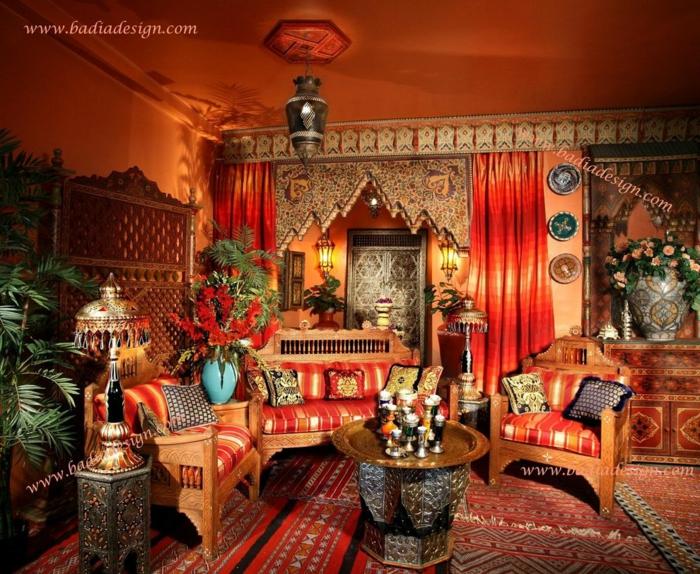 reichlich dekoriertes Haus im marokkanischen Stil, eine Liege und zwei Sessel aus Holz, Kissen mit Streifenmuster, ein Kaffee- und ein Beistelltisch mit vielen Verzierungen, Designer-Stehlampe mit metallenem Schirm, vergoldetes Servierbrett in rznder Form, viele Blumen und Pflanzen, zwei Gardinen in Rottönen, Wand und Decke gestrichen in Orange, spanische Wand aus Holz, Teppiche mit unterschiedlichen Mustern, Kommode mit einer riesigen Vase darauf, drei dekorative Wandteller