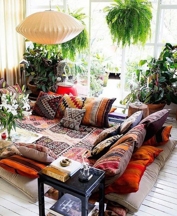 weißer Holzboden mit kleinen Musterteppichen, marokkanische Kissen mit farbigen Mustern, viele grüne Pflanzen, zwei hängende Pflanzen, Kronleuchter aus weißem Papier, Relaxecke mit Terrassenaussicht