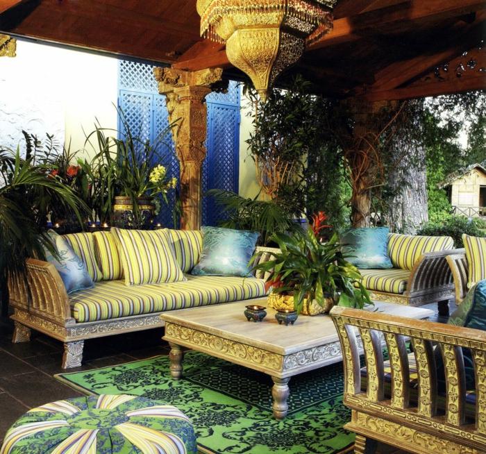 kühler Relaxort im Außenbereich mit orientalischen Einrichtung - niedrige Couch mit Streifenmuster, niedriger Tisch aus Holz, gestrichen in Weiß, Holztisch mit dekorativen Elementen, Eckcoouch mit zwei Kissen, hängende Pflanzen im Garten, Gartenlaub aus Holz, grüner Teppich mit Verzierungen, Puff mit Bezug aus Stoffapplizierungen