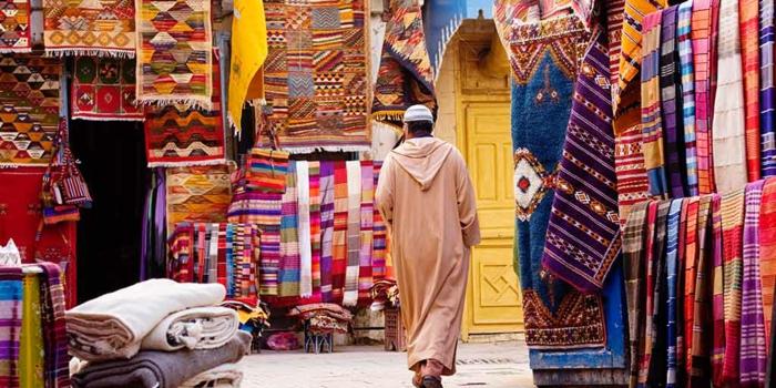 ein Mann mit hellen Kleidern auf dem Agadir Markt für orientalische Stoffe, Teppiche und Gardinen