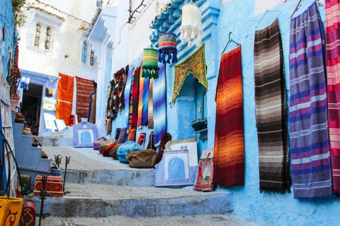die Blaue Stadt in Marokko, Straße mit Treppen - marokkanischer Markt für Dekorationen und Stoffe, Schals und Kissenbezüge, kleine dekorative Kisten aus Holz und orientalische Wandbilder
