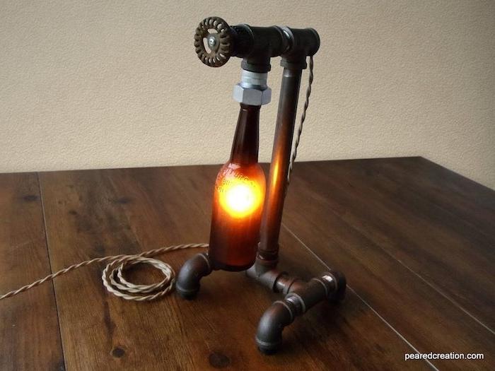 ein tisch und ein metallrohr und eine lampe mit einer braunen glasflasche -lampe mit flaschen