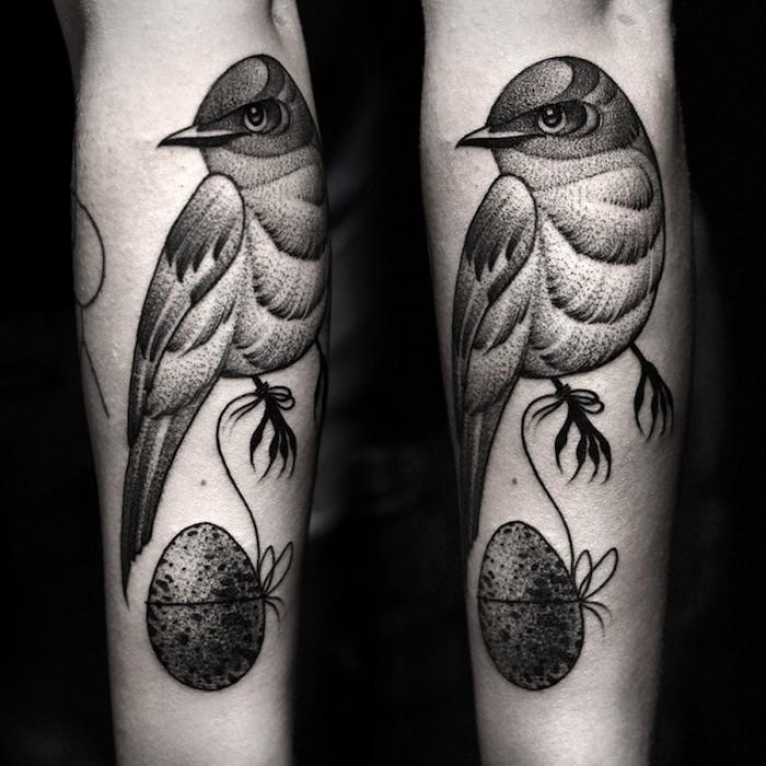 schöne tattoos, schwarz-graue tätowierung am arm, vogel mit ei