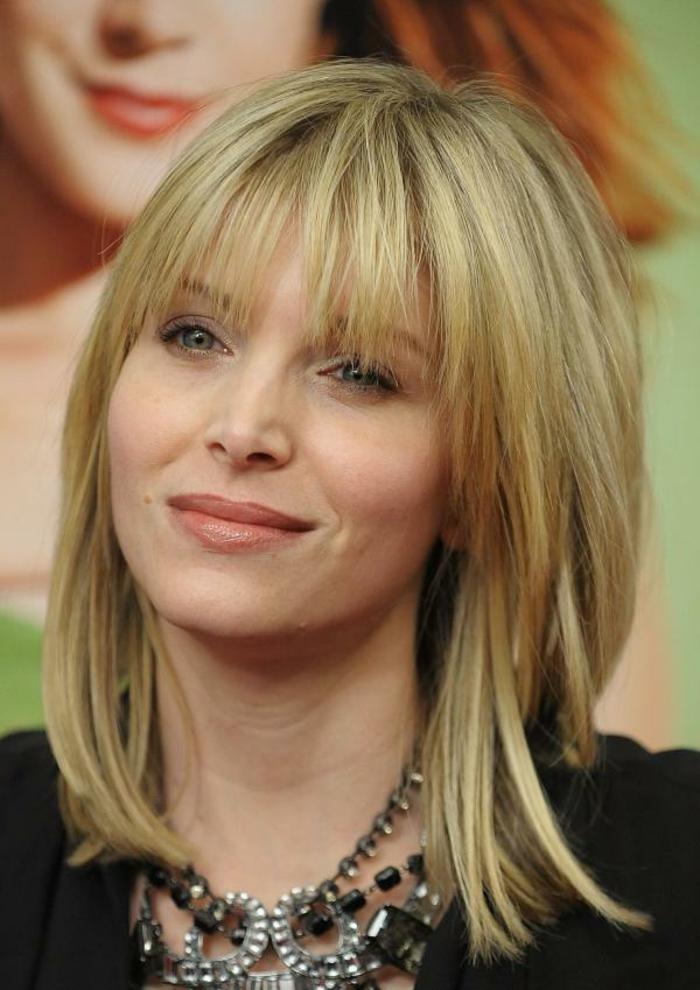 mittellanges Haar Frisur, blonde Frau mit Etagenschnitt, mit schwarzer Bluse gekleidet