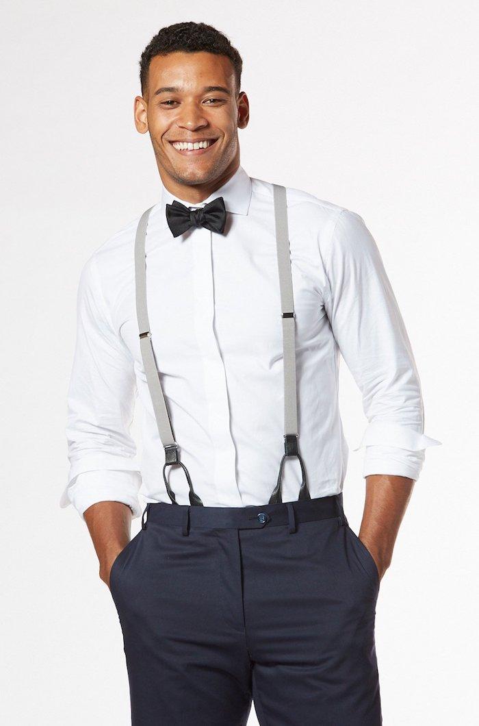 dunkelgraue hose mit hosenträger und weißes hemd anzug mit fliege lächeln model mann