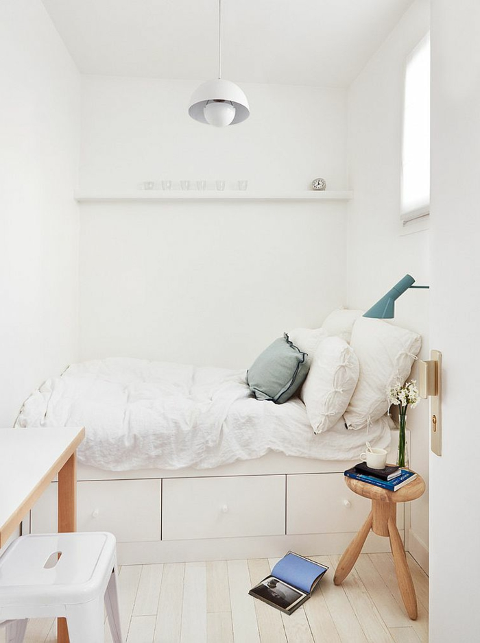 schmales Schlafzimmer in Weiß, kleines Bett mit Kasten, runder Hocker aus Hold, quadratisches Fenster über dem Betttisch, schmaler Schreibtisch mit weißem Metallstuhl
