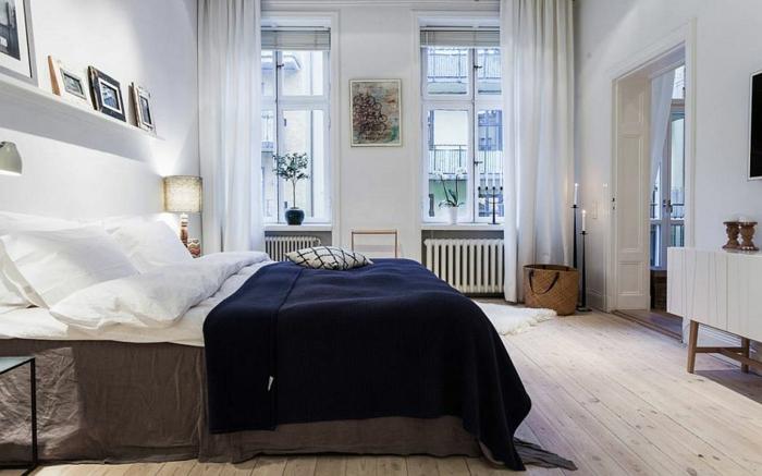 zwei schmale Fenster, Radiator unter dem Fenster, lange halbdurchsichtige Gardinen, graue Bettlacken und dunkelblaue Bettdecke, Wandregal mit Bildern, zwei große Kerzen, Übergang zum anderen Zimmer