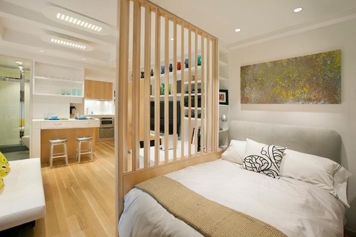 Einzimmerwohnung skandinavisch einrichten - weiße Wände mit eingebauten Regalen, Kochinsel mit zwei Metallstühlen im industrial Stil, Raumteiler aus hölzernen Gottern, Trennwand aus Holzgittern, dekorative Glasvasen aus färbigem Glas, indirekte Beleuchtung