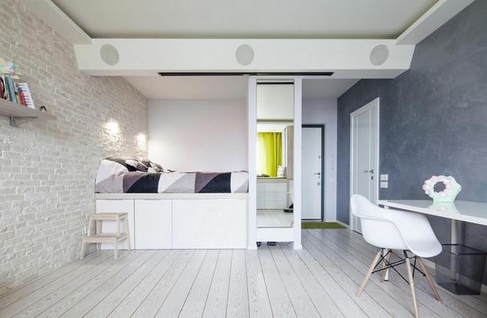 graue Wand mit Marmor-Optik, weißer Schreibtisch mit einfachem Design, schwarzer Papierkorb Metall, weißgestrichene Ziegelwand mit Bücherregal, Hochbett mit Unterschrank, Zimmer mit zwei Türen