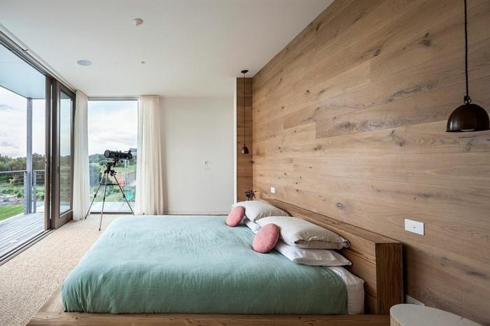 schweidische Möbel - ovaler weißer Betttisch, riesiges Bett mit Holzrahmen, türkisblaue Bettdecke in Kombination mit zwei runden rosafarbenen Kissen, Eckfenster mit langen Gardinen in weißer Farbe, Terrasse mit Holzboden, Fernglas in der lincken Ecke vor dem Fenster, Wand mit Holzverkleidung