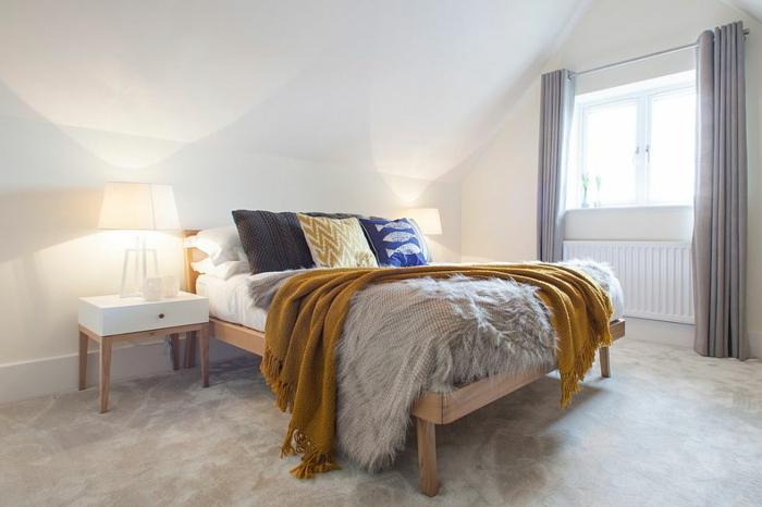 elegant gestaltetes Zimmer mit Schrägdach, Boden mit Marmor-Optik, weißer Nachttisch mit braunen Beinen, Leselampe mit weißem Schirm, blauer Kissen mit Fisch-Motiv, gelbe Kuscheldecke mit Troddeln, glaue Bettdecke aus Plüsch, kleines Fenster mit grauen Gardinen