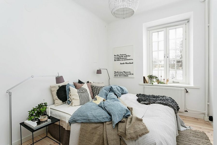 ungemachtes Bett mit vielen farbigen Decken, Holzboden mit gestricktem Teppich in grauen Farben, Flechtkronleuchter in Weiß, Wandspruch mit schwarzen Buchstaben, minimalistischer Nachttisch in Schwarz, Bett mit vielen Bettkissen