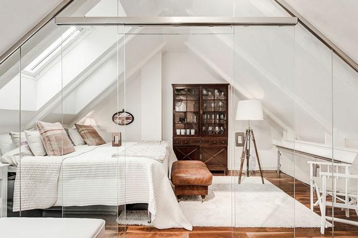 Dachzimmer mit braunem Boden, Schlafzimmer mit Glaswand, Sitzbank aus braunem Leder, weißer Plüschteppich vor dem Doppelbett, zwei große Dachfenster, Industrial-Stehlampe mit drei Beinen, dunkelbrauner Schrank mit Glastüren