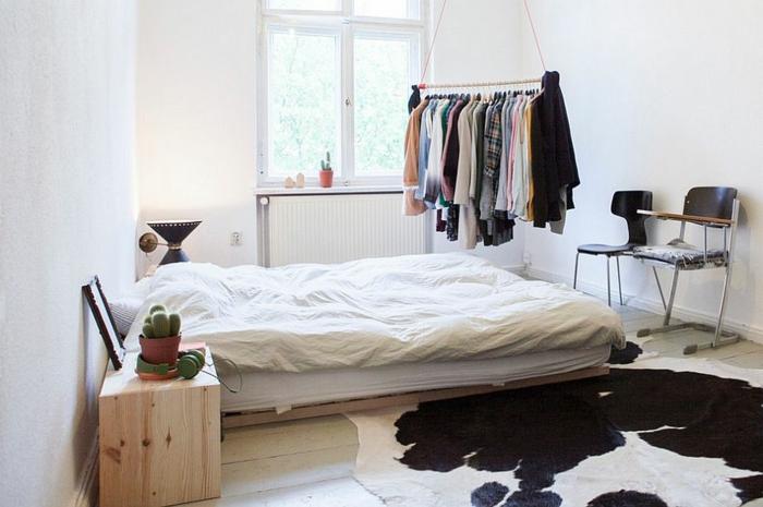 Matratze auf Europalette, DIY Hacken aus Holz mit vielen Kleidern, zwei Stühle mit minimalistischem Design, Teppich aus Tierfell, zwei kleine Kakteen, grüne Kopfhörer auf dem Nachttisch