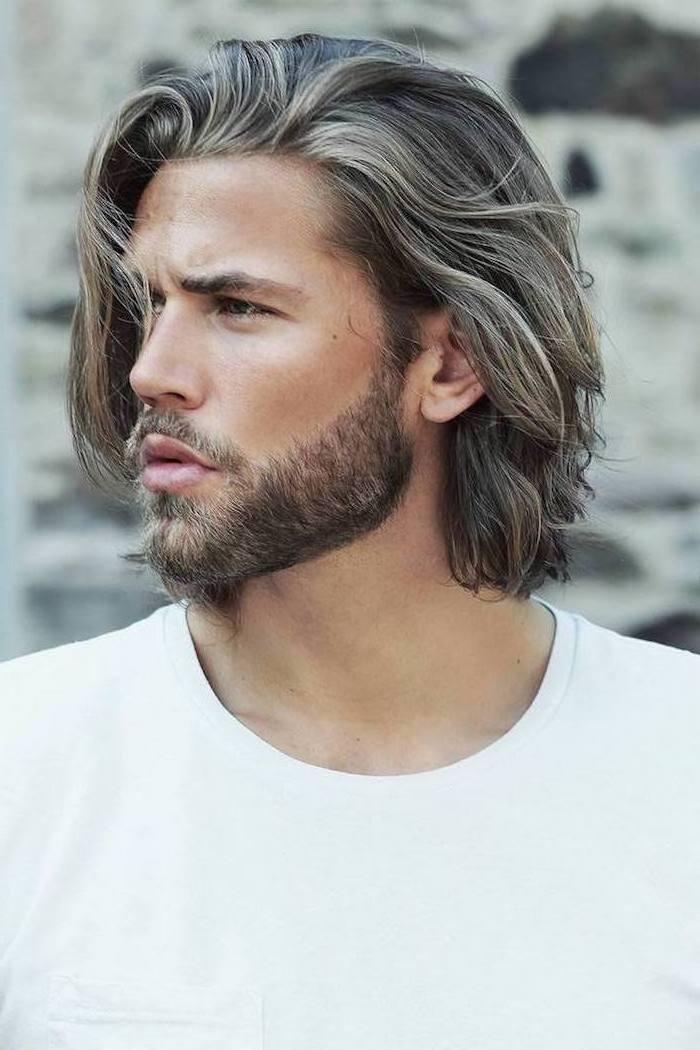 Mittellange Haare mit blonden Strähnen, olivfarbener Teint, Bart rund um den Mund, weißes Top