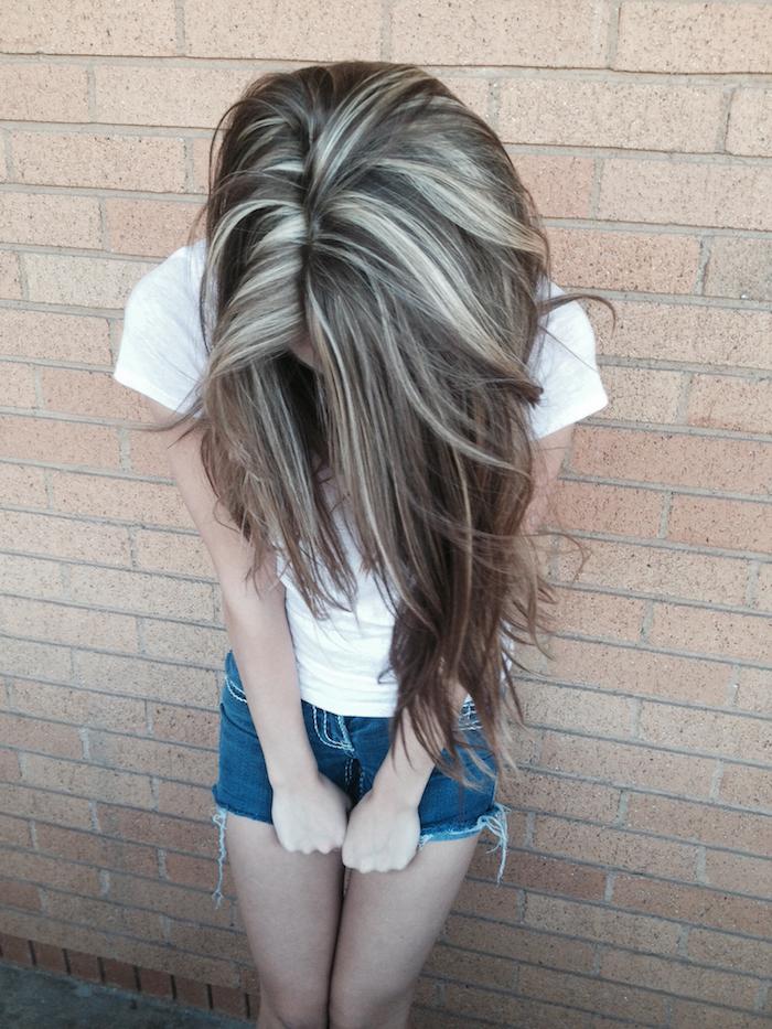 silberblonde Haare - ein Mädchen zeigt Ihr Haar, das mit silberblondem Strähnchen versehen ist