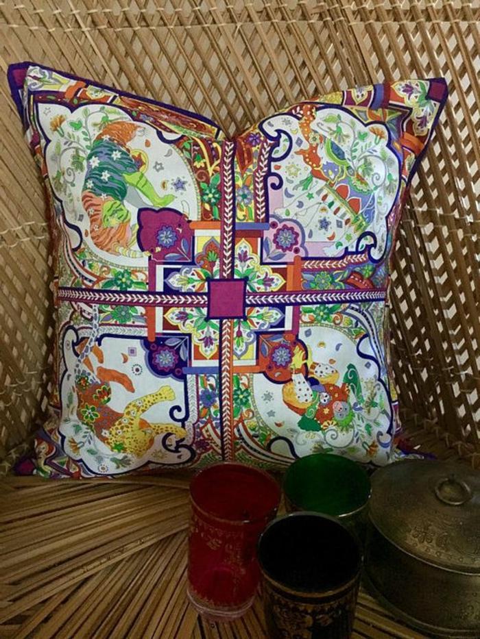 Flechtstuhl mit drei Gläsern für Tee aus farbigem Glasund einer Teekanne aus Edelstahl darauf, kleinre quadratische Kissen mit indischen Zeichnungen