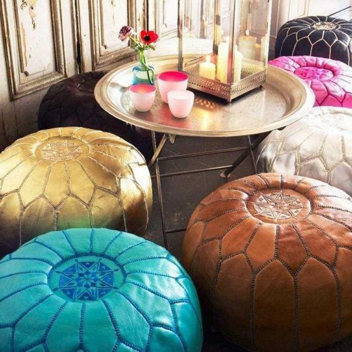 Wandverkeidung aus Holz mit veraltetem Look, runder Tisch aus Metall mit Goldabdeckung, Kerzen- und Blumendeko, viele Leder-Puffs in Kontrastfarben