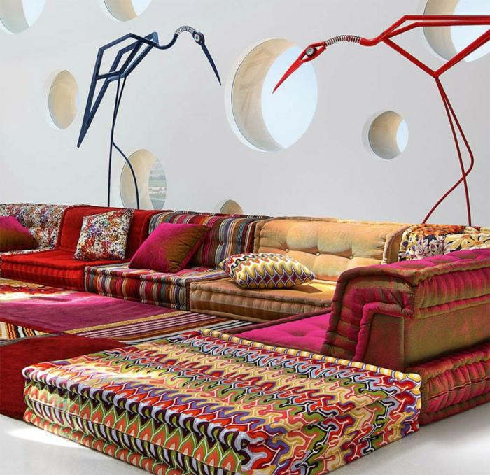 Couch aus farbigen Stoffen mit verrückten Mustern, kline Musterkissen, Plüschteppiche in grellen Farben, Wand mit runden Fenster-Nischen, zwei dekorative Kranich-Figuren