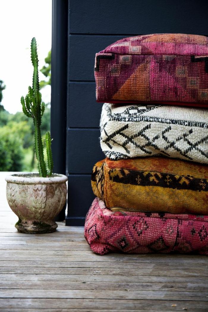 Haus mit schwarzen Wänden, Verande mit Holzboden, Keramiktopf mit einem großen Kaktus, vier orientalische Kissen mit Mustern