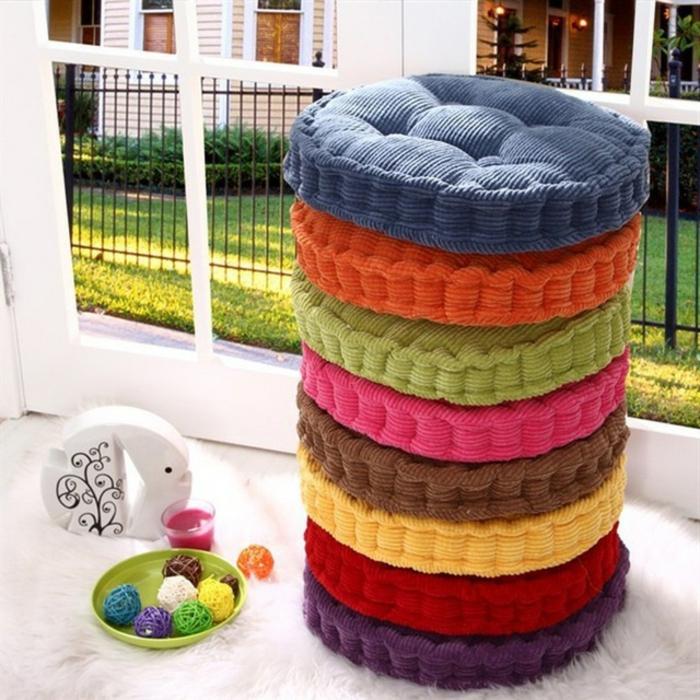 gemütliche farbige runde Sitzkissen in grellen Farben, weißer Teppich auf der Veranda, Aussicht zum Nachbarnhaus