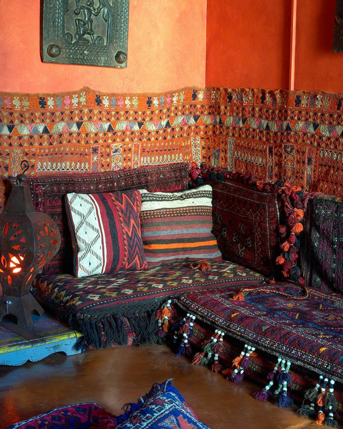 Couch in dunkle Farben, Couchdecke mit Troddeln, orange gestrichene Wand mit metallener Wanddeko, Stehleuchte aus Metall mit Schlitzerei