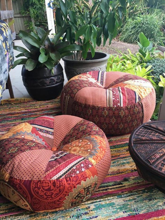 gemütliche Puffs in Terrakottafarben, vielfarbiger Teppich aus Henf, dekorativer Tisch aus Holz, gestrichen in Dunkelbraun, kleiner Gartenbereich mit vielen Pflanzen