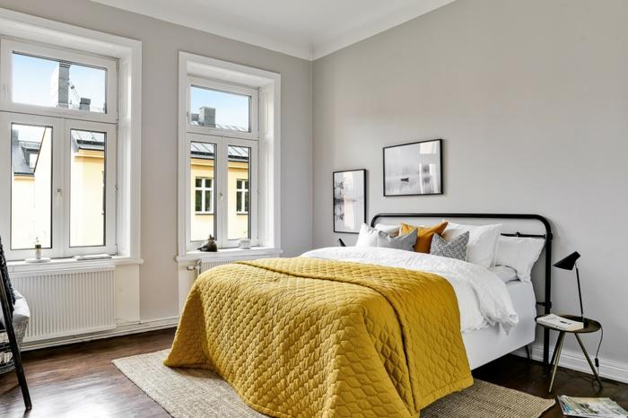 Bett mit Metall-Kopfteil, gelbe Bettdecke, minimalistischer Tisch mit runder Form, zwei kleine Fenster