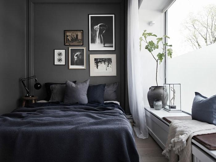 dunkelgraue Wände im Schlafzimmer, Bett in der linken Ecke, dunkle Bettkissen und dunkle Schlafdecken, Fensterbrett mit Pflanzen dekorieren, Leseecke am Fenster, Fensterglass mit Matt-Folie