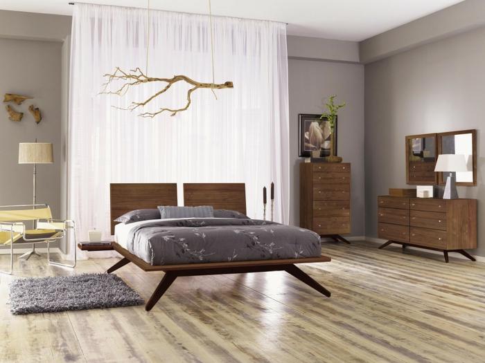 skandinavisches Schlafzimmer mit hellgrauen Wänden, halbdurchsichtigen weißen Gardinen, Doppelbett mit Kopfbrett aus Holz, graue Bettdecke mit Pflanzenmotiven, quadratische Matte aus Plüsch in grauer Farbe, Relax-Stuhl mit Metallbeinen, Rückenlehne und Sitz aus gelbem Stoff, Wanddeko aus Holz, Holzmöbel mit minimalistischem Design
