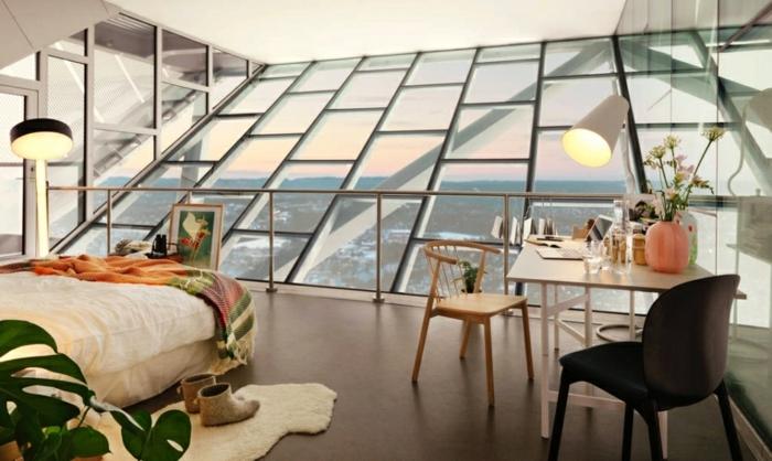 1-Zimmer-Dachwohnung, Schrägdach aus Glas mit Metallgeländer, zwei Designer-Stehleuchten, Esstisch mit zwei Stühlen, Esstisch mit Blumen dekorieren, warme und bewueme Hausstiefel, Schlafzimmer mit Glaswand