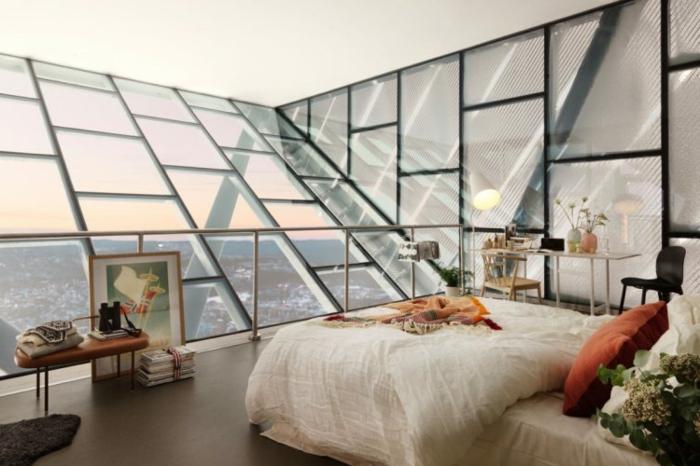 Dachwohnung mit Glaswand mit Metallgeländer, braune Sitzbank mit Ledersitz, bunte Schlafdecke und orangenfarbener Kissen, Schreibtisch mit zwei Blumenvasen, Stehlampe links dem Schreibtisch