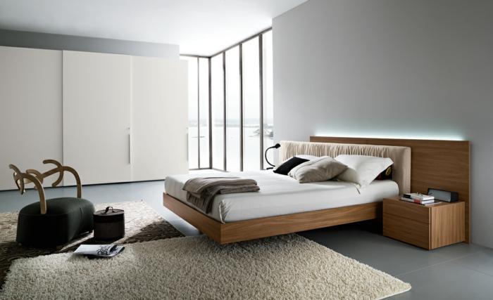 Schrank mit Schiebetüren, Eckfenster im Schlafzimmer, Holzbett mit hölzernem Kopfbrett mit LED-Beleuchtung, Designerstuhl mit schwarzem Sitz und Rücklehne aus Holz, schwarze runde Kiste mit Deckel