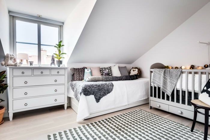 Babyzimmer skandinavisch einrichten, Babyzimmer mit Schrägdach, graues Babybett mit drei Schubladen, weiße Couch mit farbigen Kissen, weißgestrichene Kommode mit Hakengriffen, zwei grüne Pflanzen, Musterteppich in Grau und Weiß