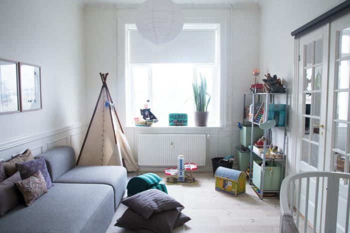 Babyzimmer mit zweiflügeliger Glastür, graue Couch ohne Beine, Kissen mit Musterbezügen, indianischer Zelt mit Triangelform, Metallregal mit Spielzeugen, runder Kronleuchter aus Papier