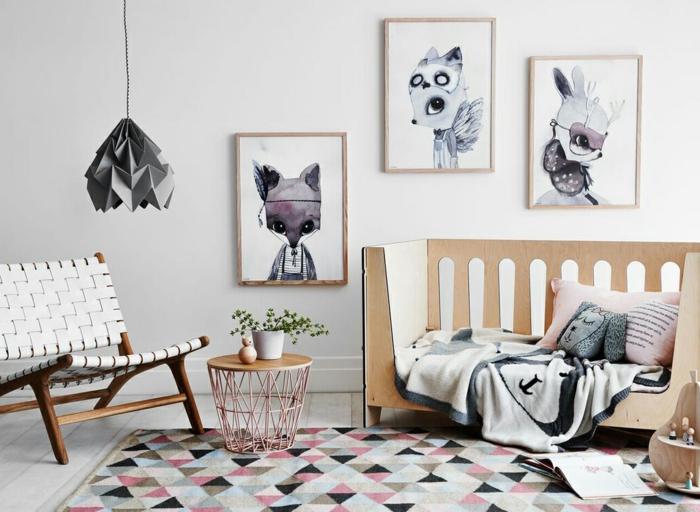 Babycouch mit Holzgittern, Teppich mit Triangel-Motiven, runder Metalltisch mit Kupferüberzug, Holzstuhl mit Ledersitz, grauer Origami-Kronleuchter aus Papier, drei Aquarellbilder, ein offenes Buch, kliener Holztisch in der Form einer Birne, rosafarbener Kissenbezug mit Spruch