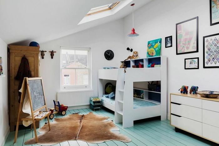 Kinderzimmer mit blauem Boden, Kinderzimmer mit zwei Betten, Teppich aus Tiefell, dekorative Elefanten-Figuren, bunte Bilder, schwarze runde Wanduhr, schwarze Tafel mit Stand, kleines Dachfenster über dem Etagenbett