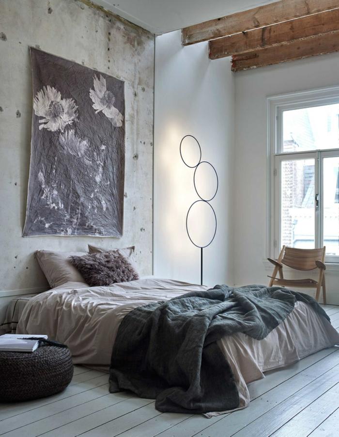 Wohnideen Schlafzimmer in Grau, Wand mit veraltetem Look, schwarz-weißes Plakatt mit Blumen, niedriges Bett mit Plüschkissen, brauner Holzstuhl mit einfachem Design, dekorativer Stand mit drei Ringen, Puff mit gestricktem Bezug