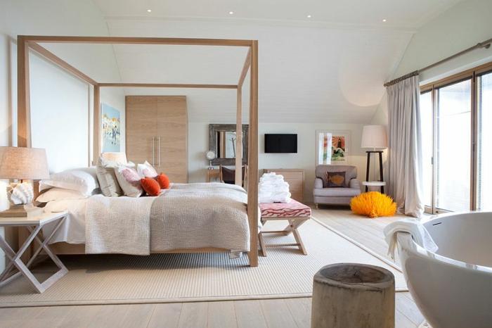 Doppelbett mit Baldachin, dekorative Kissen in Orangefarbe, Sitzbank mit Holzbeinen, orangenfarbener Puff vor dem grauen Armstuhl, Zimmer mit indirekter LED-Beleuchtung, Schlafzimmer mit runden Badewanne