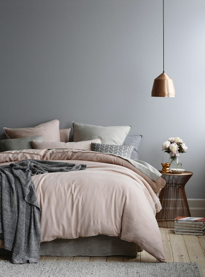 grau gestrichene Wand, Kuscheldecke in Aschenrosa, weiche Kissen mit Plüsch, minimalistischer Tisch aus Kupfer mit weißen Blumen in einer Glasvase