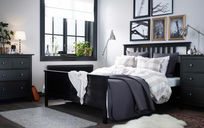 schwarze Einrichtung, Fenster mit schwarzem Rahmen, graue Fußmatte vor dem Bett, zwei Stehlampen mit beweglichem Stand, Blumendeko im Schlafzimmer