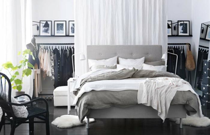 einfacher wohnen - weißer Vorhang als Raumteiler, Ständer mit schwarzen Kleidern, schwarzer Flechtstuhl mit weißem Kissen, zwei kleine Plüschmatten in Weiß, schwarze Ikea-Kisten zur Aufbewahrung
