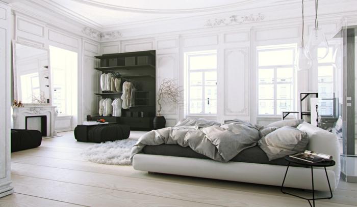 luxuriöses Zimmer in skandinavischem Stil mit Holzpaneelen an der Wand, Zimmerdecke mit Ornamenten, Lederbett mit Designer-Beistelltisch, Kronleuchter aus Glas, dekorativer Kamin mit einem riesigen Spiegel darüber, offener Kleiderschrank mit offenen Regalen
