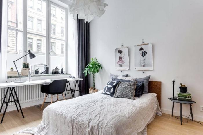 zwei Plakatte an der Bettwand, niedriger Tisch mit untypischem Design, langer weißer Schreibtisch mit schwarzen Beinen gestellt vor dem Fenster, graue Gardinen bis zum Boden, Designer-Kronleuchter aus Papier
