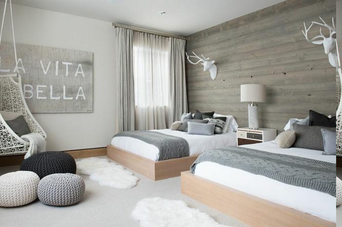 Kinderzimmer mit zwei Betten, Wandbild mit Spruch, Wand verkleidet mit Holz, zwei weiße Dekoelemete-Hirchkopf, Nachttisch in der Mitte, drei Puffs mit Strickbezügen, Hängestuhl